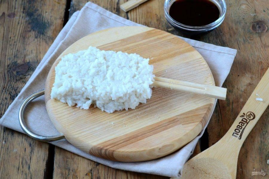 Из половины риса сформируйте лепешку, на ее середину положите деревянные палочки, и заверните, чтобы по форме лепешка напоминала мороженое.