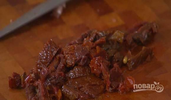 Достаньте из банки сушеные помидоры и нарежьте их при помощи острого ножа на небольшие кусочки.