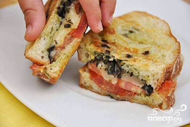6. Выложить сэндвич на гриль и жарить до хрустящей золотисто-коричневой корочки. Перевернуть сэндвич и жарить до золотисто-коричневой корочки с другой стороны, пока сыр не расплавится. Дать сэндвичу немного остыть и подавать.