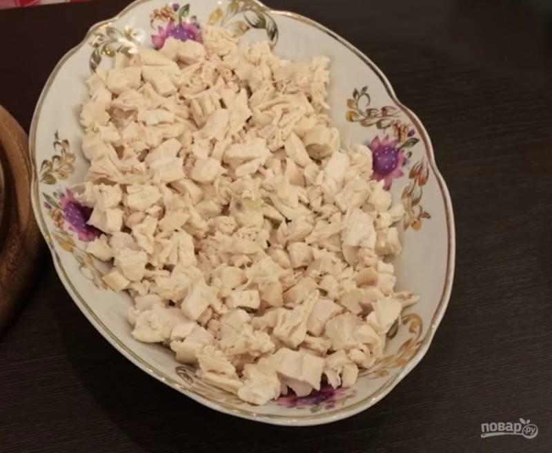 Отваренную куриную грудку я нарезаю кубиками и сразу выкладываю первым слоем на тарелочку, в которой буду подавать салат.
