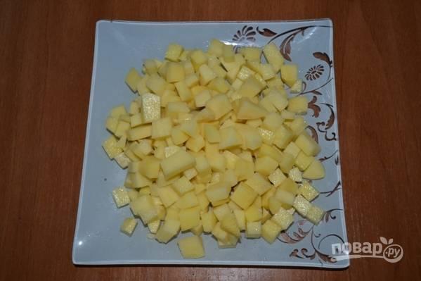 Картофель очистите от кожуры и нарежьте небольшими кубиками. Затем перекладываем его в кипящую воду и варим минут 5.