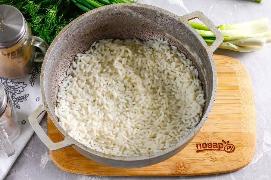 Рис промойте в воде, высыпьте крупу в казан или емкость с антипригарным дном, влейте теплую воду и отварите примерно 15 минут с момента закипания воды на умеренном нагреве. Накройте крышкой и дайте крупе пропариться еще 5-7 минут, затем вынесите кашу на холод и остудите примерно 30 минут.