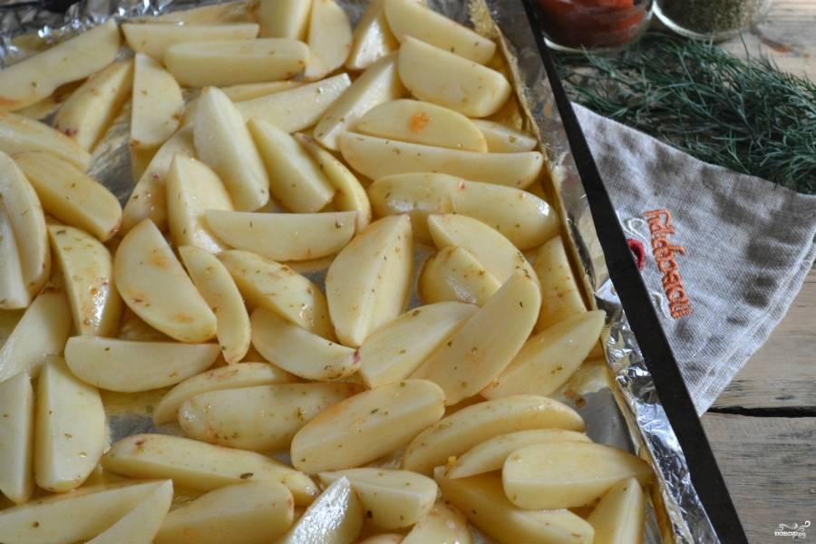 Противень застелите пергаментом или фольгой. Выложите в один слой кусочки картошки. Поставьте его в разогретую до 180 градусов духовку на 30-40 минут. За 10 минут до окончания готовки посыпьте мелко нарубленным чесноком.