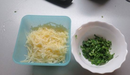 Пока масса закипает, нарежьте кинзу и натрите сыр.
