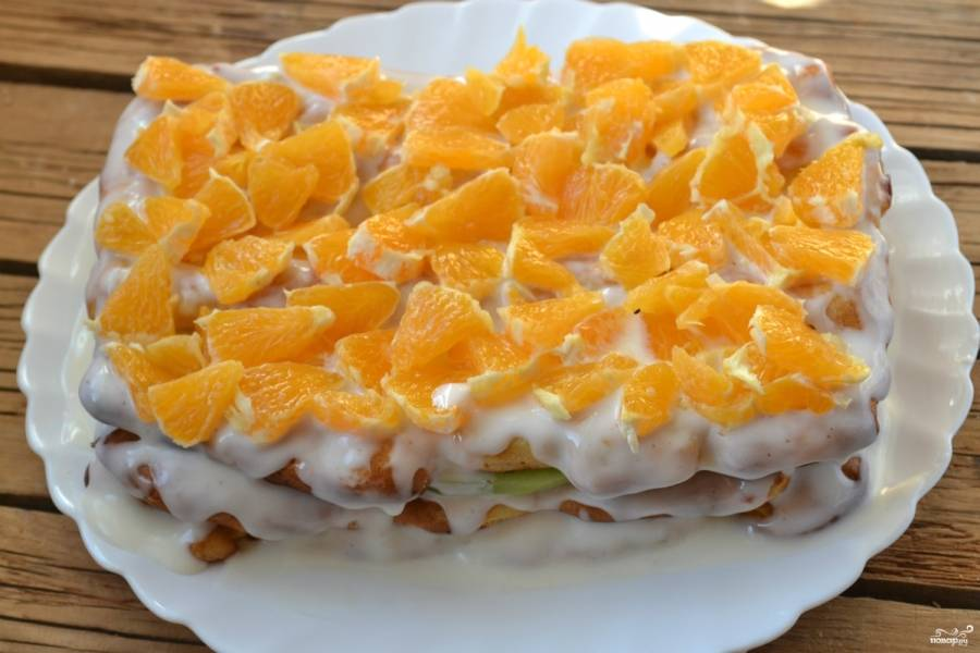 """Положите сверху третий корж, залейте торт остатками крема так, чтобы тот покрывал торт и сверху, и по бокам. Украсьте торт измельченным апельсином. Отправьте его в холодильник минимум на 2 часа, чтобы он пропитался и стал """"единым целым""""."""