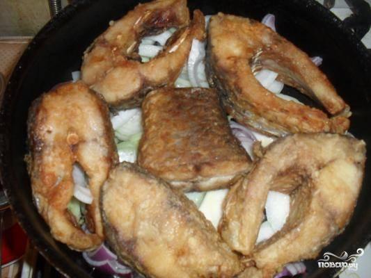 2. Теперь Рыбу достаем, а на дно сковороды выкладываем лук (масло я рекомендую сменить, или вообще тушить в другой сковороде), затем - обжаренную рыбу, и под крышкой на маленьком огне тушим, пока лук не станет мягким.