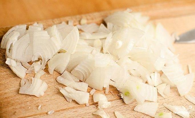 В кастрюле разогрейте оливковое масло (3 ст.ложки) на среднем огне. Лук почистите и нарежьте, обжарьте его в кастрюле (4 минуты).