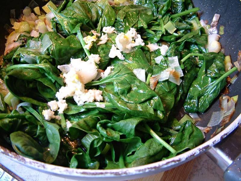 2. Обжарим на сковороде лук-порей (белую часть) в растительном масле до мягкости. Далее добавим шпинат, перемешаем. Добавим пропущенный через пресс чеснок, закрываем крышкой, даем овощам чуть потушиться. Добавим затем сметану и специи по вкусу.
