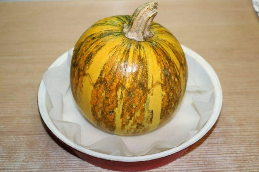 Накройте тыквенной крышечкой. Поставьте в форму для запекания, предварительно застелив ее пекарской бумагой.  Тыкву смажьте растительным маслом.