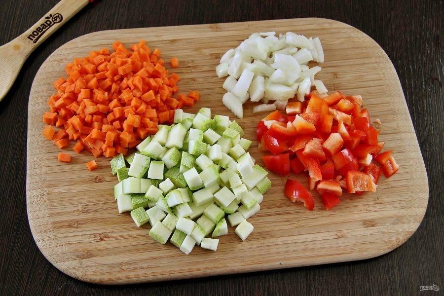 Лук, морковь, перец и кабачок нарежьте небольшими кубиками.
