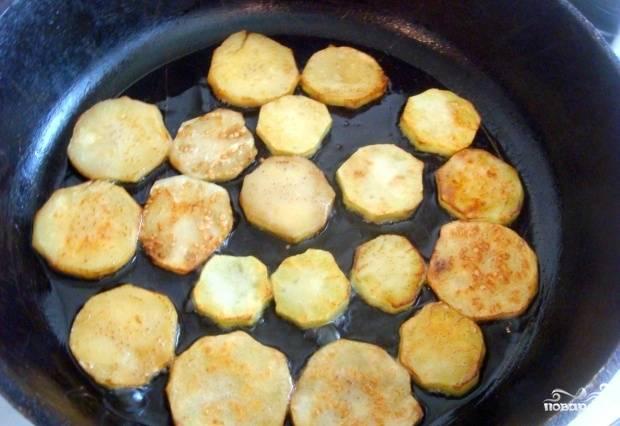 Разогрейте растительное масло на сковороде и обжарьте на нём баклажаны с двух сторон. Не жалейте масла, так как баклажаны его активно впитывают при обжаривании.