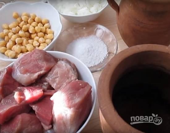В первую очередь замочите нут в холодной воде на ночь. А уже с утра готовим суп. Нарежем баранину на кусочки, очистим и мелко нарежем лук.