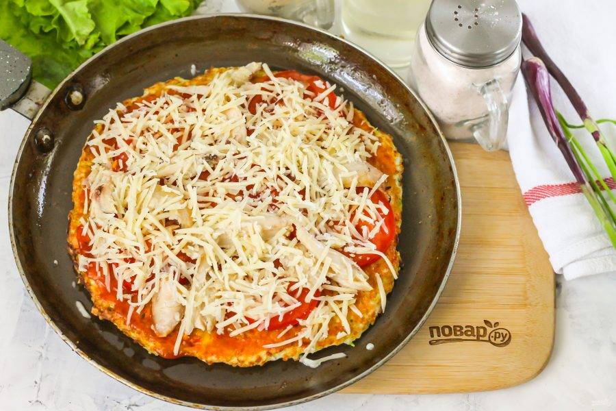 Натрите твердый сыр на терке с мелкими ячейками, выложите сверху помидоры и мясо. Прикройте сковороду крышкой и протомите блюдо примерно 2-3 минуты до расплавления сыра.