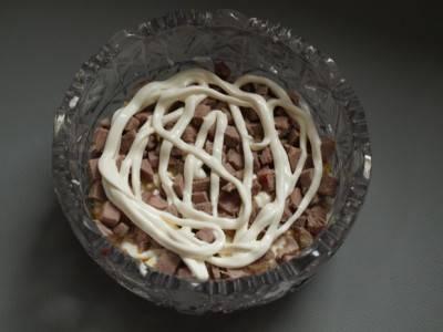 Говядину порежьте небольшими кусочками, уложите на яйца и залейте майонезом.