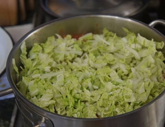Рыбный бульон необходимо процедить, добавьте в него томатную смесь. Посолите, подождите, пока закипит, и добавьте фасоль и капусту.