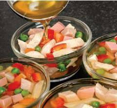 Бульон от курицы остудить до комнатной температуры. Засыпать желатин и дать ему набухнуть, перемешать. Затем на плите  сильно нагреть, но не доводить до закипания. При необходимости подсолить, и добавить черный перец и кориандр. Убрать с огня и процедить через чистое сито или марлю. В формочки для заливного или обычные чашки разложить смесь мяса и овощей, влить куриный бульон и поставить в холодильник на ночь. Заливное можно легко извлечь из формочек, перевернув их вверх дном и прикрыв на несколько секунд полотенцем, смоченным в горячей воде.