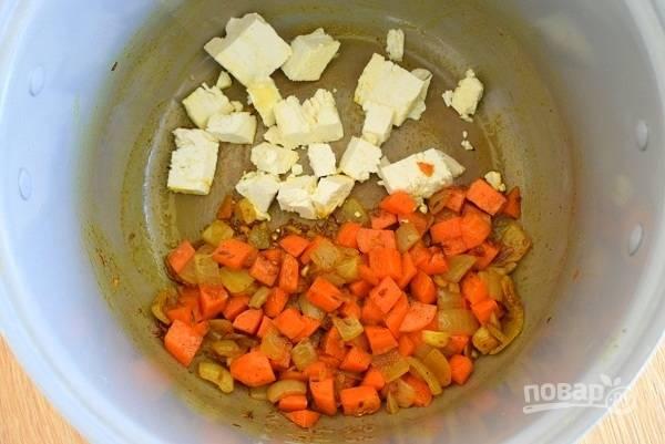 Положите морковь,  обжаривайте в течение 5 минут, помешивая лопаткой. Добавьте кубики адыгейского сыра, перемешайте.