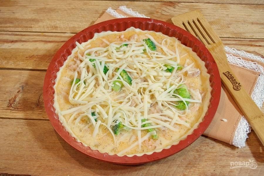 Натрите на терке твердый сыр. Выложите его на пирог.