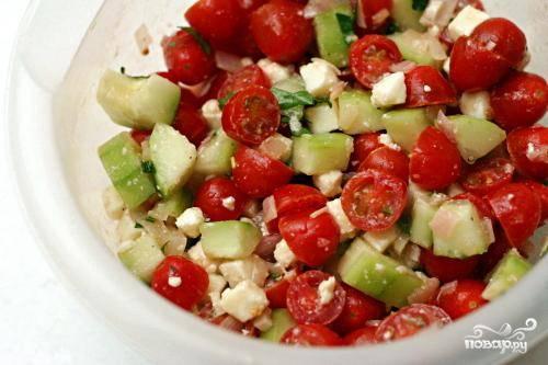 3. Добавить огурец, измельченные оливки, раскрошенный сыр Фета, приготовленную томатную заправку и измельченную зелень петрушки в миску с помидорами. Аккуратно перемешать и подавать.