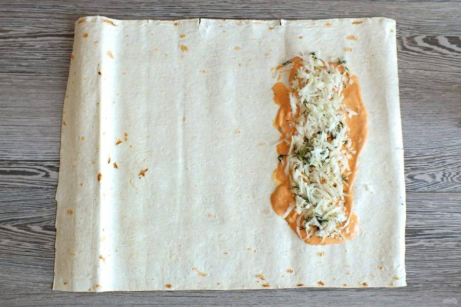 Лаваш разложите на столе.  Отступите от края и намажьте обильно соусом. Визуально разделите все ингредиенты на 2 части. Выложите 1/2 часть капусты.