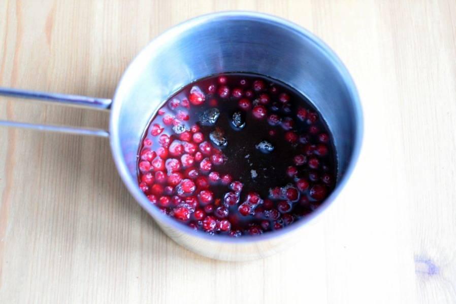 Сварите пряный сироп из воды, сахара, вина, клюквы и пряностей. В процессе варки клюкву раздавливайте толкушкой для пюре.