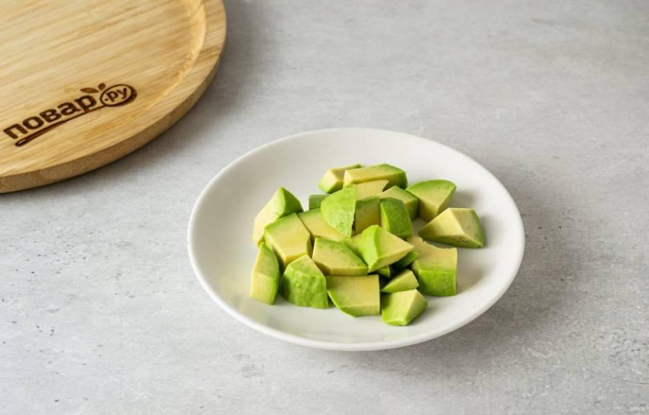 Авокадо очистите от кожуры, удалите косточку. Нарежьте на ломтики среднего размера. Сбрызнете их лимонным соком.
