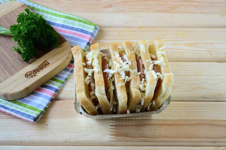 Затем вложите их в подходящую форму для запекания. Сверху дополнительно присыпьте оставшимся сыром моцарелла.