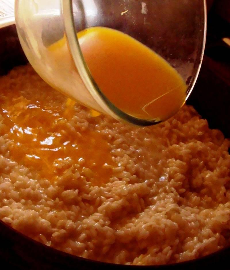 Добавляем рис и жарим до прозрачности пару минут. Вылить вино на сковородку, дождаться, когда все впитается в рис и затем добавлять бульон.