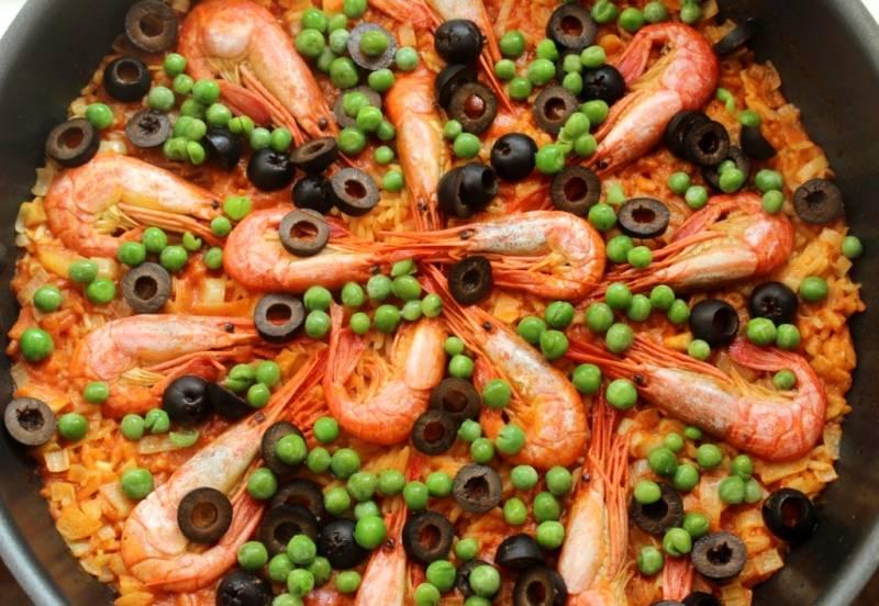 Через 10 минут открываем крышку, выкладываем  на поверхность риса нарезанные маслины и зеленый горошек. Накрываем сковороду крышкой и еще минуту готовим паэлью на сильном огне. Затем выключаем огонь и оставляем блюдо под закрытой крышкой еще на 10-15 минут. Готовую паэлью подаем к столу украсив дольками лимона. Приятного всем аппетита!