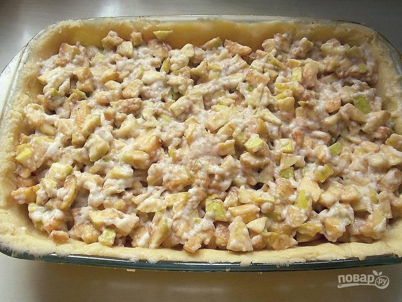 Смешайте яблоки с 1/2 частью крема, распределите на тесте. Сверху распределите вторую половину крема.