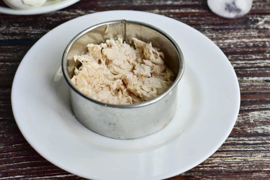 Вареное мясо нарвите руками и выложите в формировочное кольцо, которое установите на блюдо.