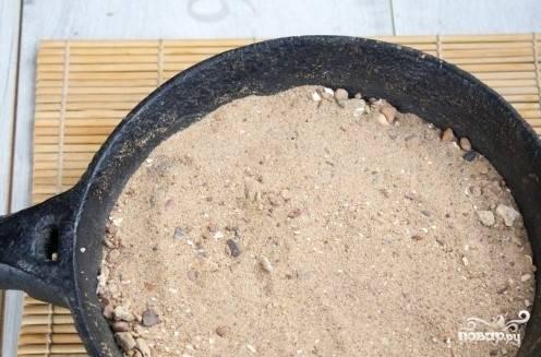 4. Подготовьте песок для приготовления кофе. Для этого в чугунную сковородку насыпьте мелкие камешки. Сверху засыпьте песком. Поставьте на сильный огонь. После того, как раскалится песок, поставьте турку в центр сковородки. Также можно использовать наименьшую конфорку, включив самый маленький огонь.