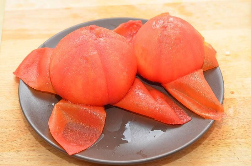 Шумовкой извлекаем помидоры и очищаем от кожицы, когда они немного остынут.