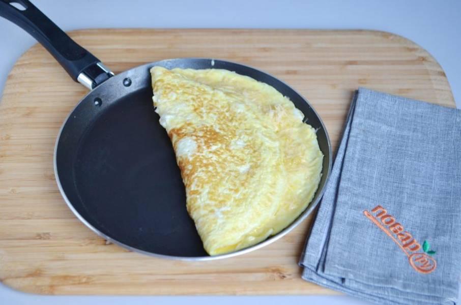6. За минуту до полной готовности омлета посыпьте одну его половину сыром. Осторожно лопаткой заверните омлет, накрыв сырную половинку и готовьте омлет еще 30 секунд.