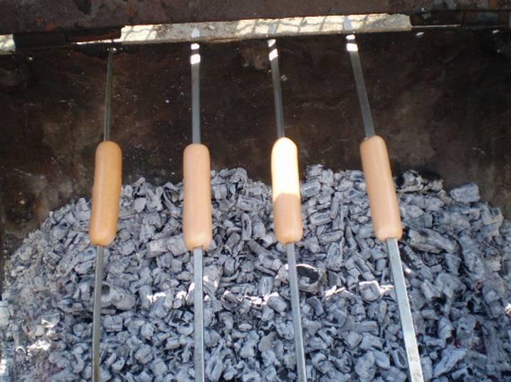 4. Когда огонь немного убавится, перегорит, устанавливаем шампура на мангал. Жарим сосиски по пару минут с каждой стороны.