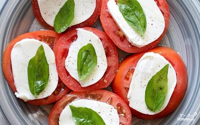 Уложите в тарелку сначала помидоры, затем сыр Моцарелла. Полейте их оливковым маслом. Положите на ломтики сыра по листику базилика. Посолите и поперчите по вкусу.