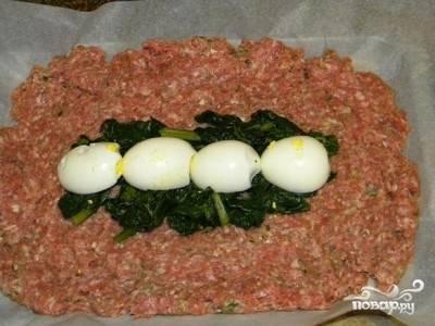 Посередине мясного пласта выложите часть шпината и вареные яйца.