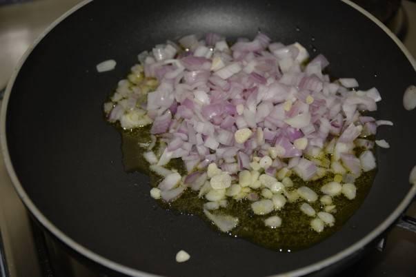 2. Пока маринуется рыбка, можно приступить к овощам. На небольшой сковороде разогреть растительное масло. Очистить и нарезать мелкими кубиками луковицу и немного чеснока. Отправить на сковороду и обжарить до прозрачности.
