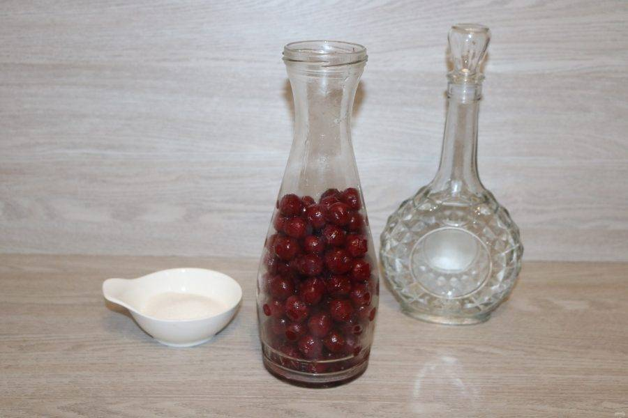 Вишню разморозьте, дайте стечь воде, поместите в ёмкость, в которой будет настаиваться вишнёвка. Насыпьте сахар.