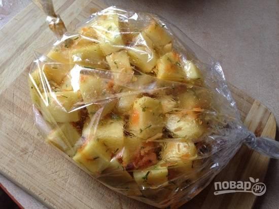 Перекладываем картофель в пакет для запекания, плотно завязываем концы пакета и делаем иголкой штук 5 дырочек в верхней части пакета.