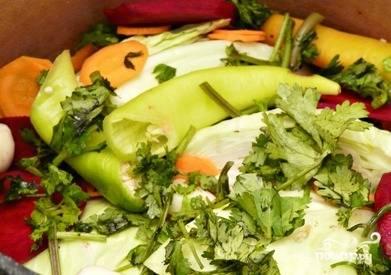 Возьмите большую кастрюлю или бочку. Уложите пару листьев капусты на дно, затем уложите кочаны, выкладывая в пространства между ними все остальные овощи и нарезанную кинзу.