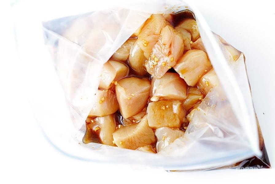 """1.Для приготовления домашнего соуса """"Терияки"""" тщательно перемешайте вместе 7 последних ингредиентов. Деревянные шампура замочите в большой кастрюле с водой за 30 минут до приготовления блюда. Куриные грудки нарежьте небольшими кубиками и перемешайте с половиной количества соуса """"Терияки"""". Сложите в герметично закрытый контейнер и охладите в течение 20 минут."""