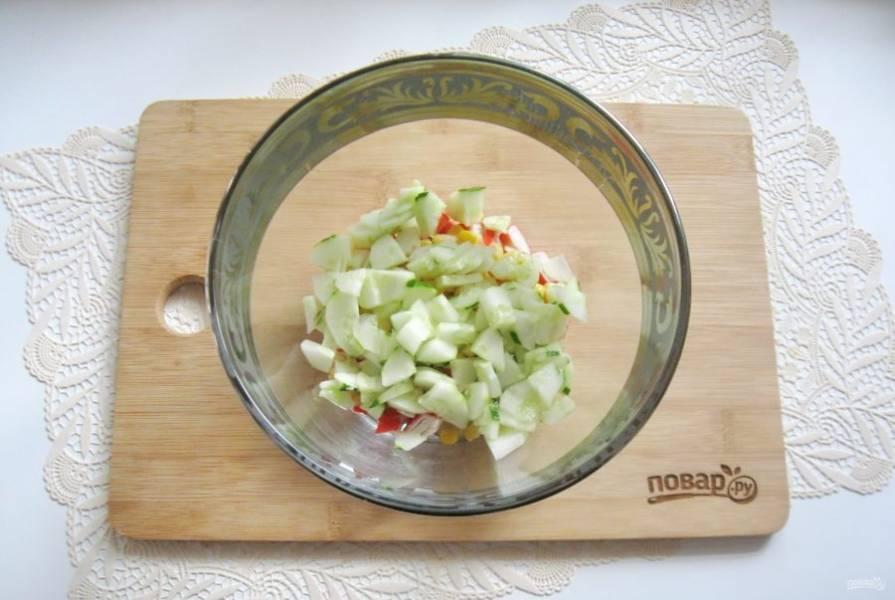 Огурец помойте, очистите и мелко нарежьте. Добавьте в салат.