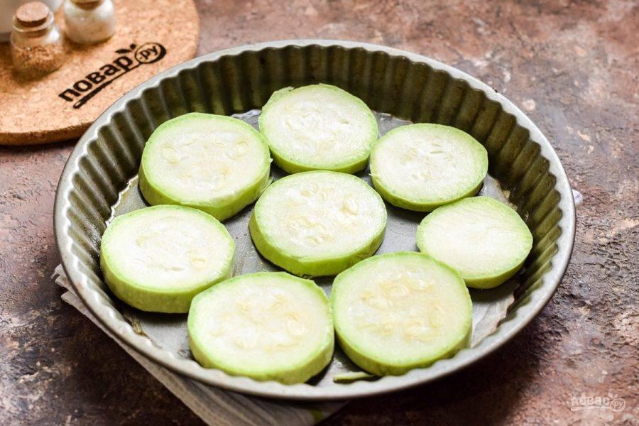 Противень хорошо смажьте растительным маслом, выложите нарезанные кружочками кабачки.