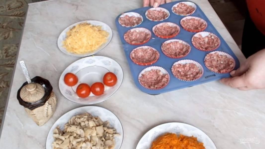 Укладывайте фарш в формочки для кексов, внутри делая небольшое углубление для начинки.