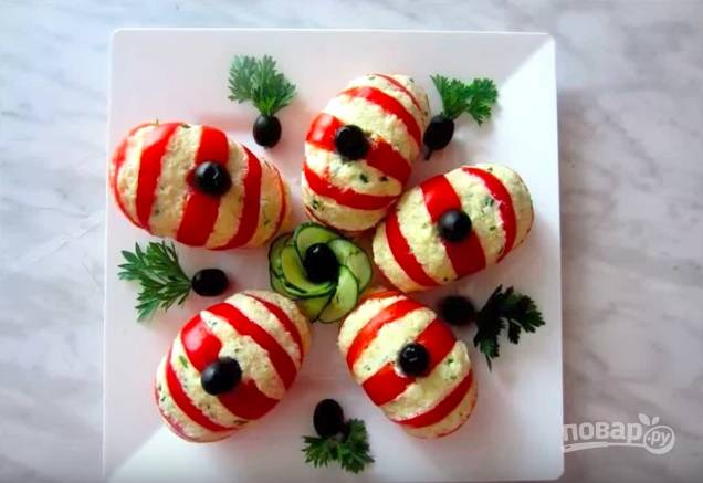 Выложите помидоры на блюдо, положите маслины на места, где была плодоножка. Украсьте блюдо.