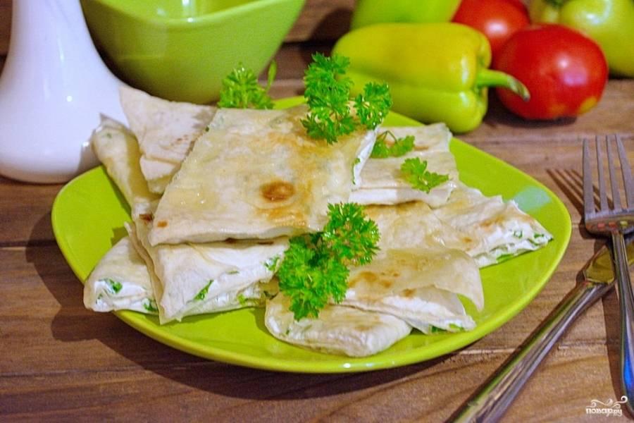 Лаваш нарежьте на квадратики. При помощи кисточки смажьте верхнюю часть квадратика растительным маслом. Выложите квадратики лаваша на противень и запеките в духовке 10 минут.