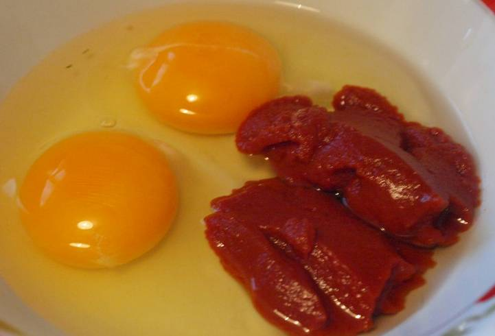 Яйца смешиваем с томатной пастой и солью по вкусу.