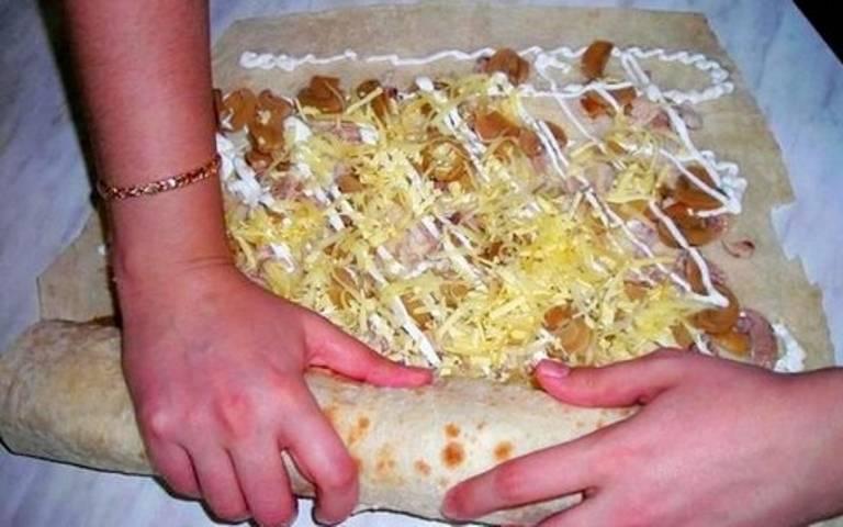 Обильно посыпьте тертым сыром и заверните лаваш с начинкой в рулет.