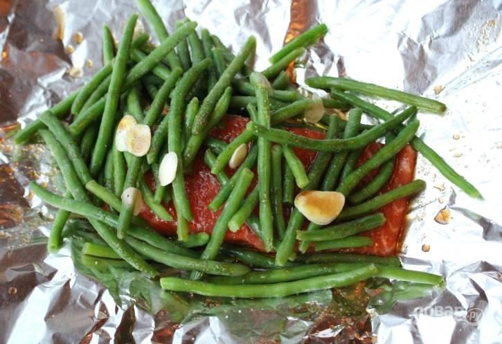 2. Затем в фольгу выложите рыбу. Смажьте её соусом. Сверху распределите чеснок и фасоль. Посыпьте их солью и перцем.